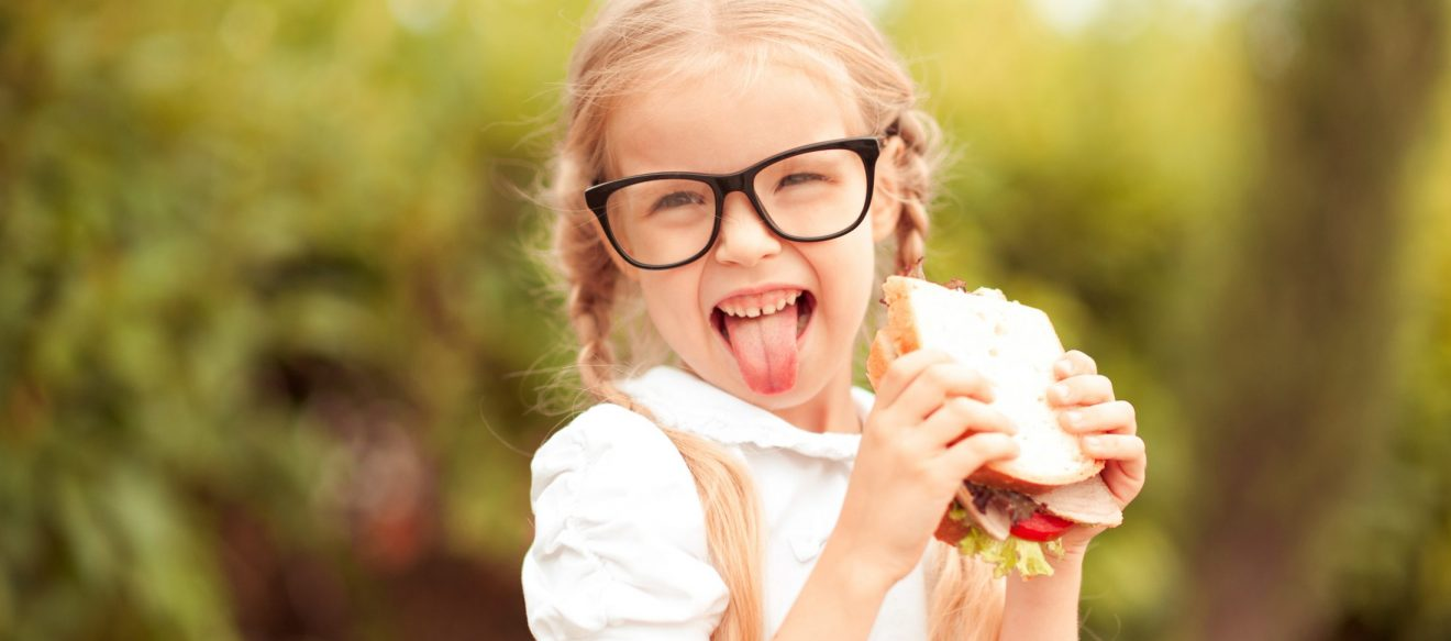 Funny,Kid,Girl,Eating,Sandwich,Outdoors.,Having,Fun.,Looking,At